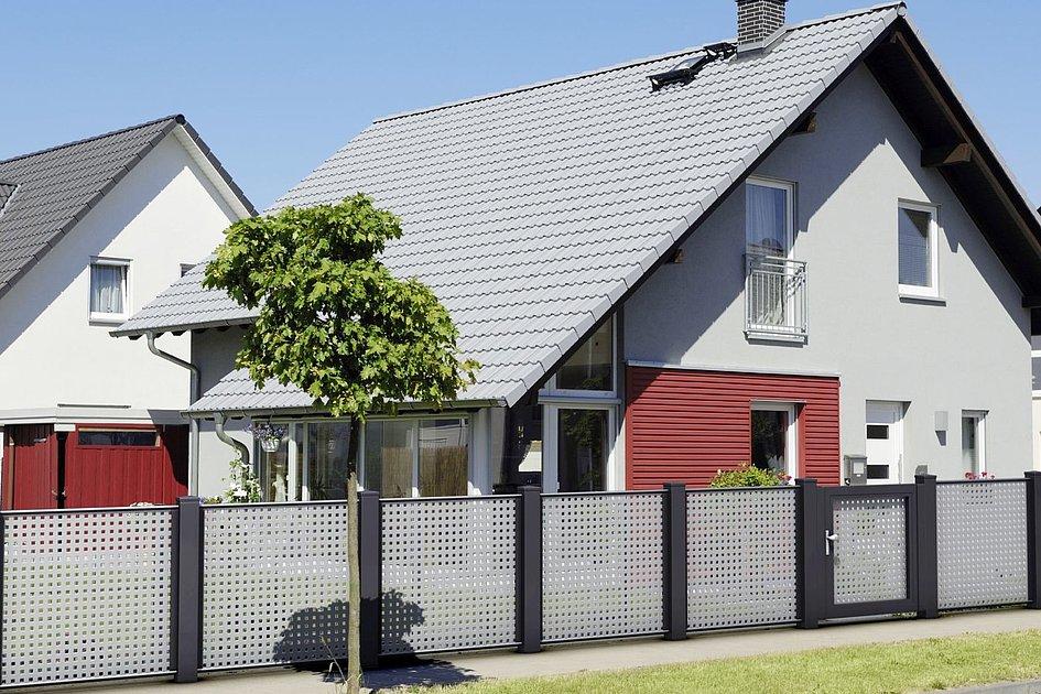 Lochblechzaun in hellgrau mit dunkelgrauen Säulen passend zu Einfamilienhaus mit grauen Schindeln