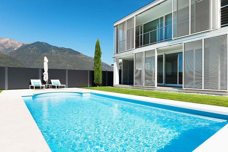 Architektenvilla mit Pool umzäunt von einem modernen Sichtschutzzaun aus Aluminium - Blick auf die Berge