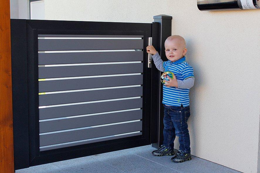 Kleinkind steht an Gartentür in modernem Design mit Sichtschutz