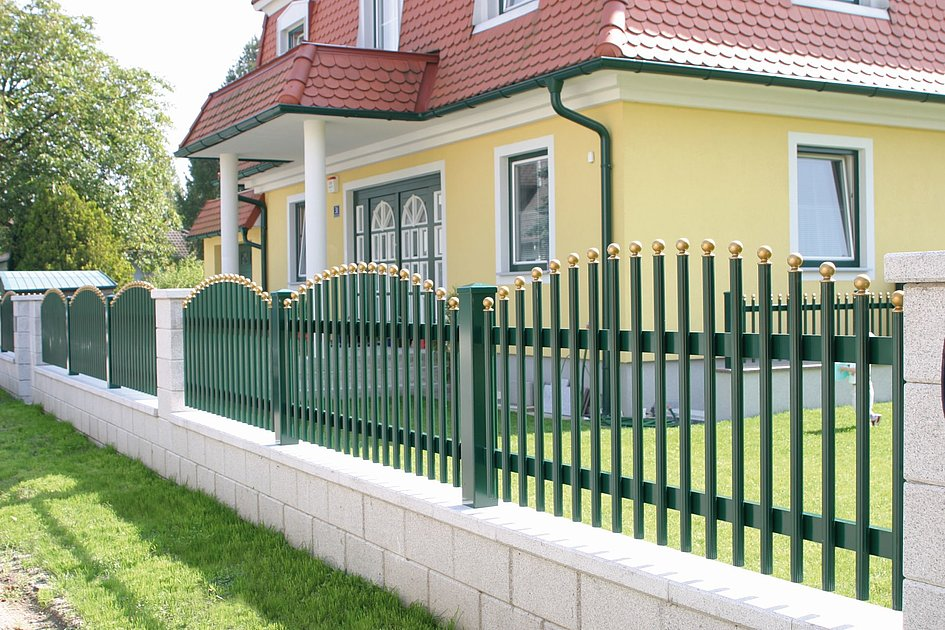 Palisadenzaun aus Aluminium in grün mit goldigen Abschlusskappen vor einem Einfamilienhaus