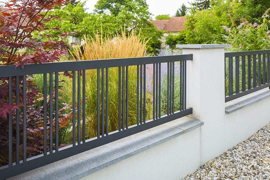 Gartenzaun aus Aluminium in grau auf Mauer und betonierten Säulen