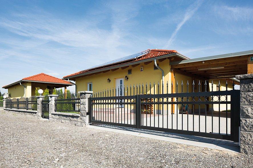 elegantes Doppelflügeltor mit Stabzaun und Gartentür in anthrazit mit Verzierungen vor großem Anwesen mit mediterranem Haus