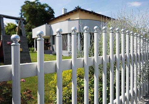 Aluminium-Stabzaun in weiß vor einem Haus mit Garten und Klettergerüst
