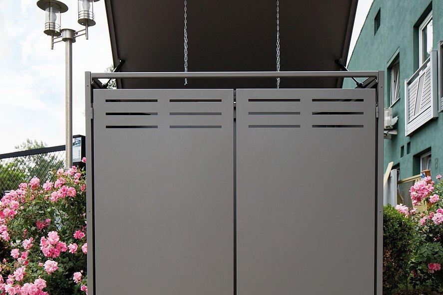 moderne graue Mülltonnen von vorne in Einfahrt mit geöffnetem Deckel