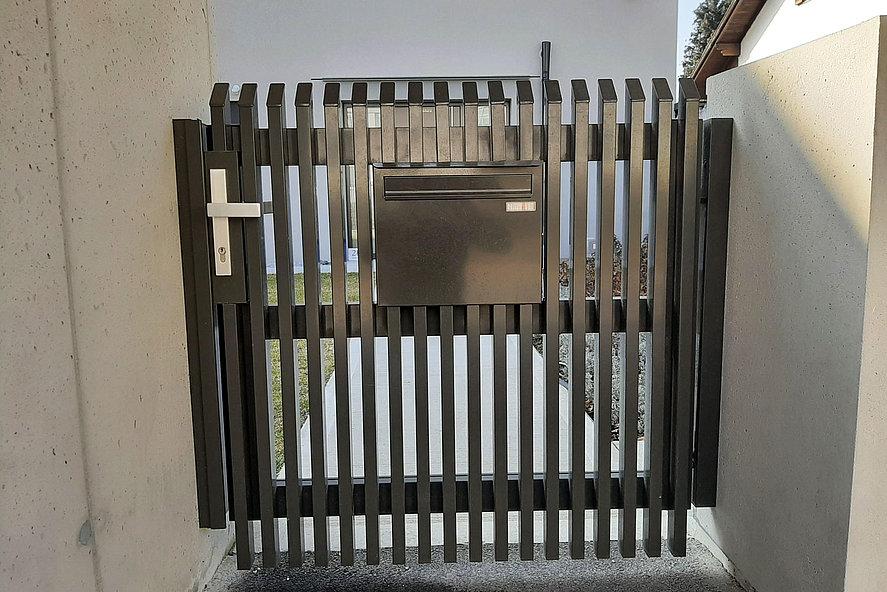 Bild von einer Pforte aus Aluminium mit Latten und Schrägkappen mit integriertem Briefkasten von Super-Zaun