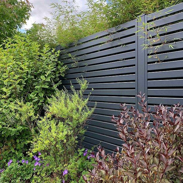 Moderner Gartenzaun mit Querlatten aus Aluminium in anthrazit in einem Garten zwischen diversen Sträuchern montiert