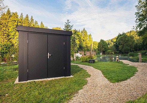 Moderne Gartenhütte aus Stahl in anthrazit steht auf einem großen Grundstück vor einem Teich
