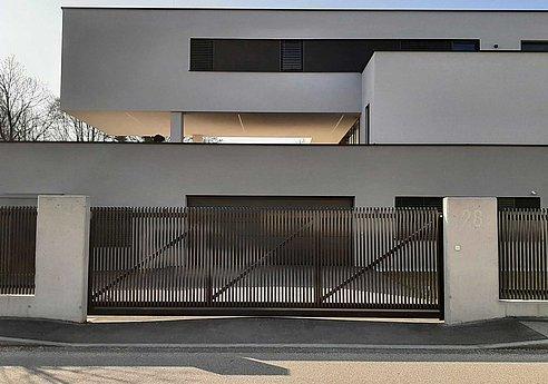 Schiebetor im Stil eines Lattenzauns mit Schrägkappen vor einer Einfahrt eines modernen Einfamilienhauses