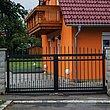 Doppelflügeltor aus schwarzen Stäben aus Aluminium zum Stabzaun um ein orangenes Haus