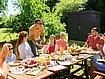 Junge Familie sitzt am Gartentisch beim Essen, im Hintergrund eine moderne Gartenhütte