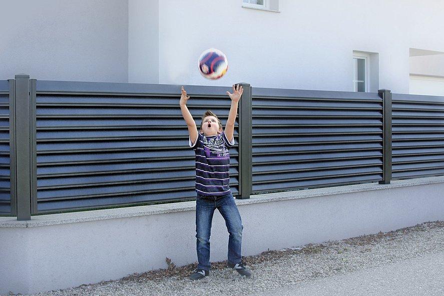 Kind wirft Ball vor Gartenzaun mit Lamellen in anthrazit auf weißem Mauersockel
