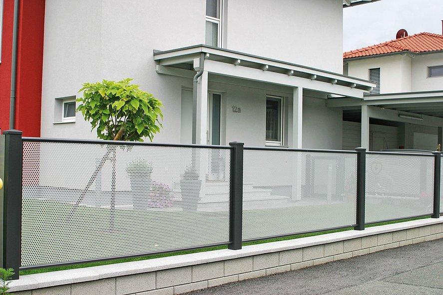 Nahaufnahme des Gartenzaun mit Lochblech in grau und anthrazit in einer Wohnsiedlung