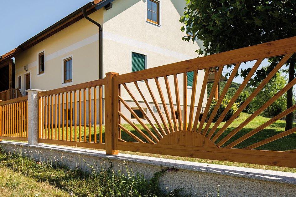 Lattenzaun in Holzoptik mit Sonnenelement vor traditionellem Haus mit Garten