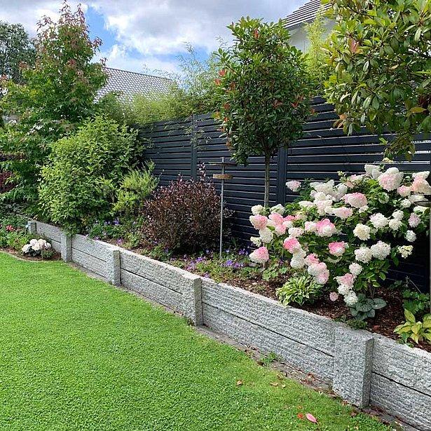 Bild von einem Garten mit einem reich bepflanzten Blumenbeet, dazwischen ein moderner Gartenzaun mit Querlatten aus Aluminium in anthrazit montiert