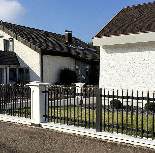 Palisadenzaun in schwarz-gold zwischen klassischen Mauersockeln in einer Einfamilienhaussiedlung