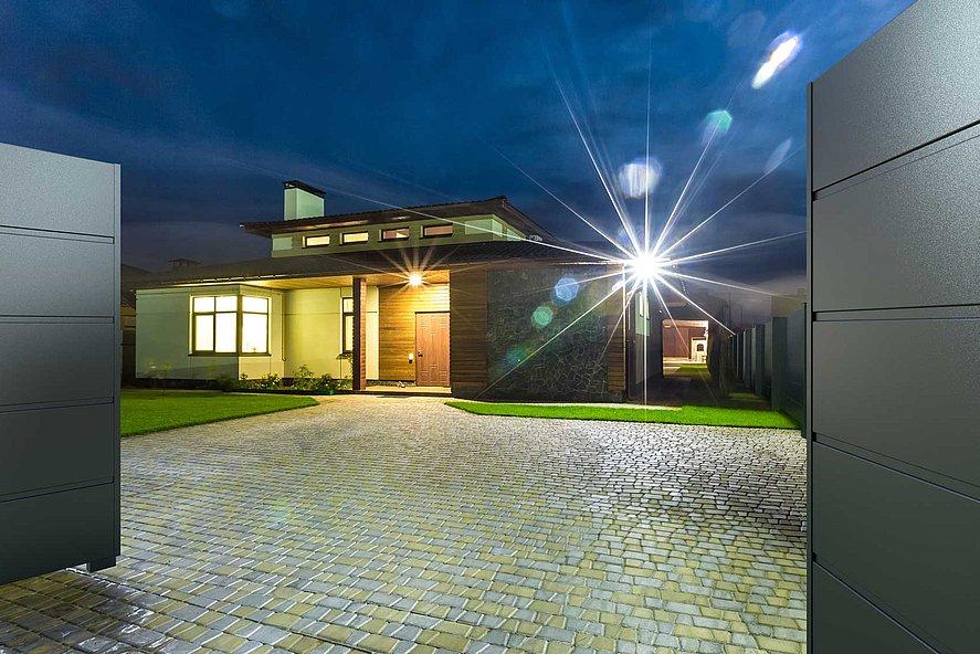 offenes Doppelflügeltor mit Sichtschutz erlaubt Blick in die Einfahrt einer modernen Villa bei Nacht