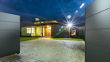 Komplett blickdichtes Zweiflügeltor aus Aluminium geöffnet, man sieht dahinter ein beleuchtetes Einfamilienhaus in der Nacht