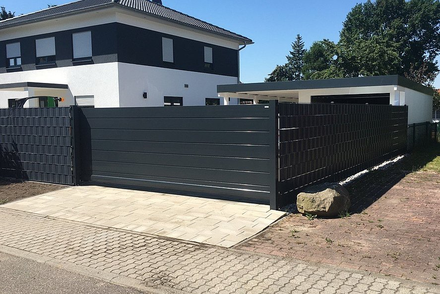 modernes Schiebetor mit Sichtschutz zum Sichtschutzzaun in anthrazit umrandet großes Einfamilienhaus