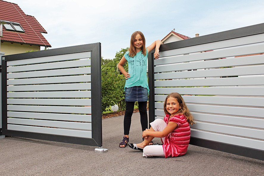 Jugendliche stehen in Doppelflügeltor aus modernen Alulatten in grau mit anthrazit