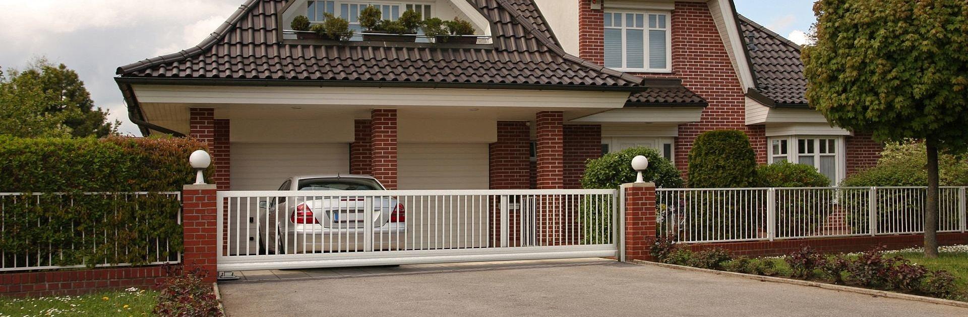Staketenzaun aus Aluminium in weiß mit Gartentor als Umzäunung für ein Einfamilienhaus im klassischen Stil