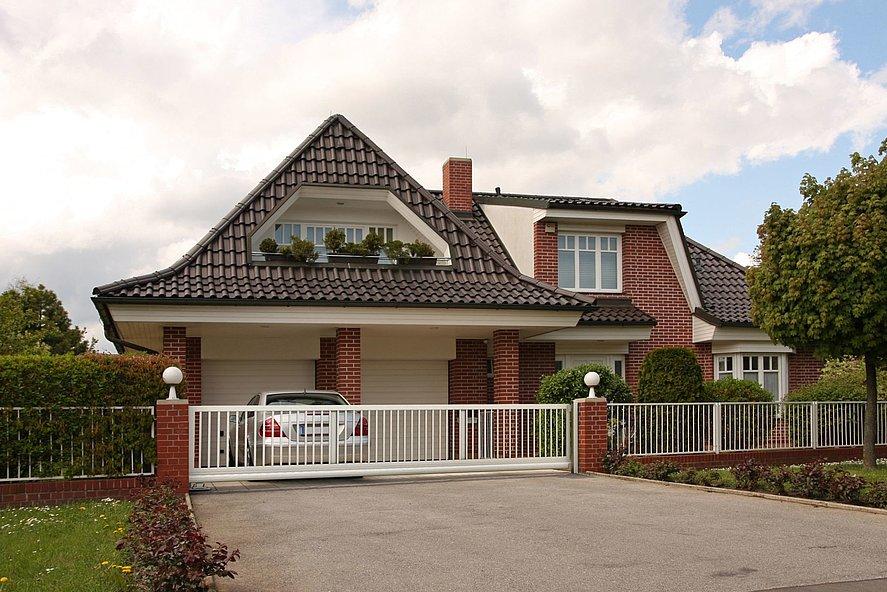 weißes Schiebetor mit Stabzaun vor herrschaftlichem Haus mit Backsteinfassade