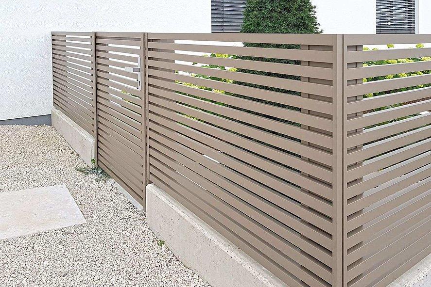 klarer, moderner Gartenzaun mit Gartentür in edlem sand auf dezentem Sockel