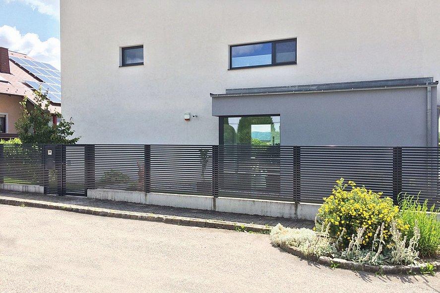 moderner Gartenzaun mit Querlatten in anthrazit vor modernem Kubushaus