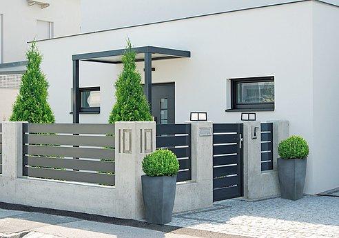 Zaun mit breiten Querlatten in der Farbe anthrazit und einer Pforte eingebaut in einer Betonmauer