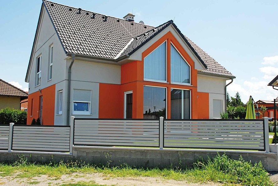 Lattenzaun zweifärbig mit Querlatten in grau vor einem Haus im Stil der 90er Jahre