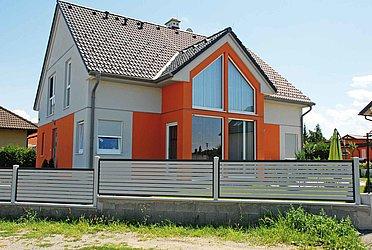 Moderner Gartenzaun mit Querlatten aus Aluminium in grau auf einer Mauer montiert vor einem Einfamilienhaus in orange