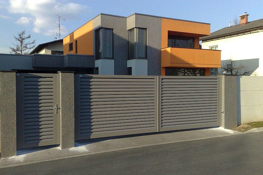 Gartentür und Schiebetor aus grauen Lamellen nvor modernem Architektenhaus in orange und grau