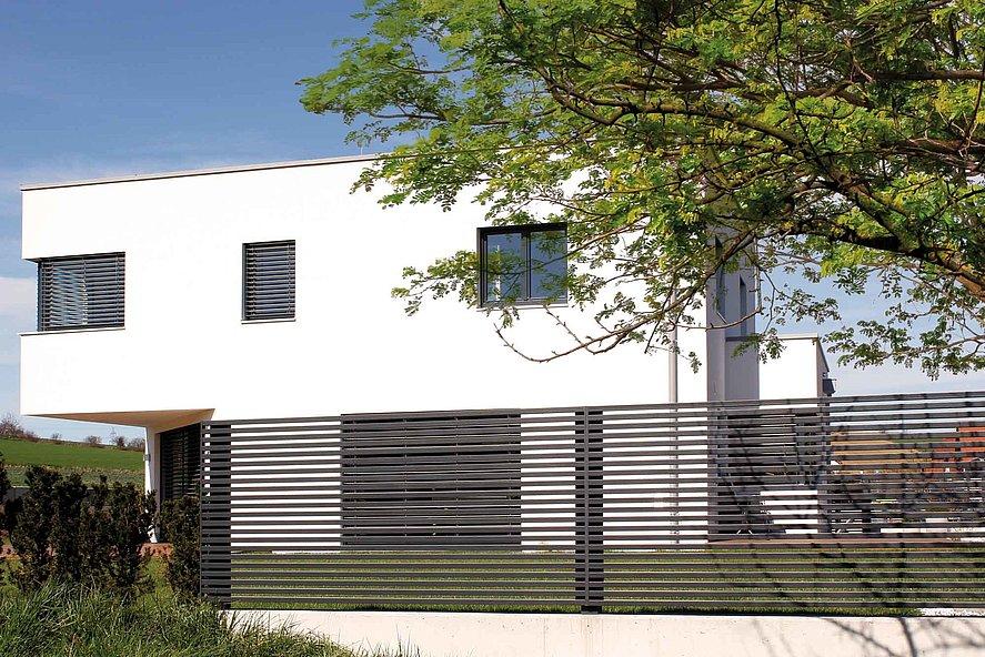 Gartenzaun ganz modern mit klaren Querlatten in anthrazit vor kubischem Haus