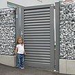 Gartentür mit Lamellen in grau als Eingang zum Gabionenzaun mit kleinem Mädchen in der Einfahrt