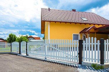 Klassisches Zweiflügeltor mit Latten neben einer dazu passenden Gartentür aus Aluminium in weiß vor einer Einfahrt