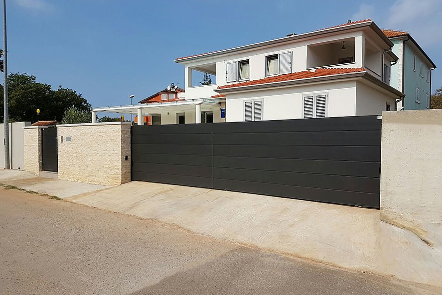 elektrisches Schiebetor und Gartentür mit Sichtschutz zur gemauerter Einfriedung als Schutz für eine moderne Villa im Hintergrund