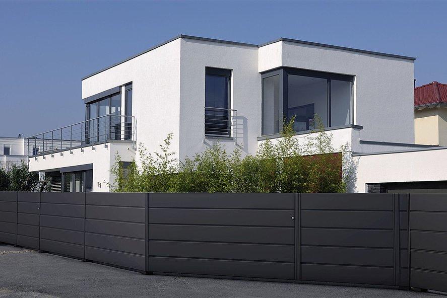 moderner Gartenzaun mit Sichtschutz in anthrazit vor neuem Architektenhaus mit viel Glas