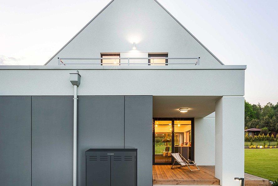 moderne Mülltonnenbox in anthrazit steht vor modernem Einfamilienhaus mit Spitzdach und Terrasse