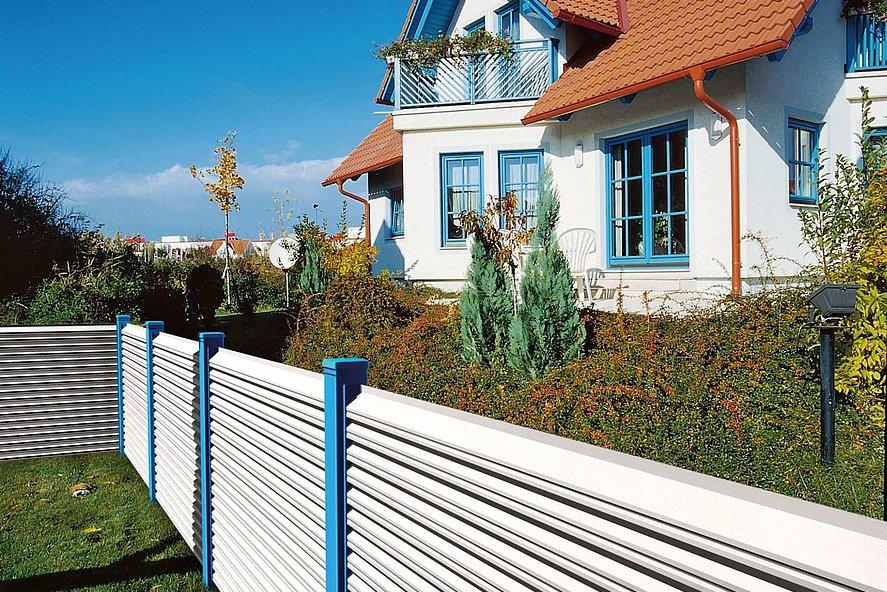 Gartenzaun mit weißen Lamellen und blauen Zaunpfosten unrahmt ein Haus im Stil der 90er mit blauen Fensterrahmen