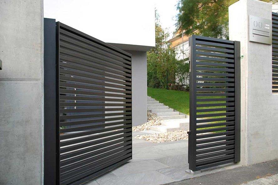 modernes Gartentor zischen Mauuersockeln steht offen vor modernem Haus