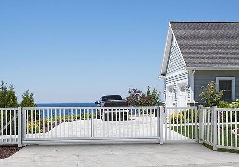 großes Schiebetor in weiß mit Stabzaun als Einfahrt zu einem Haus auf den Klippen