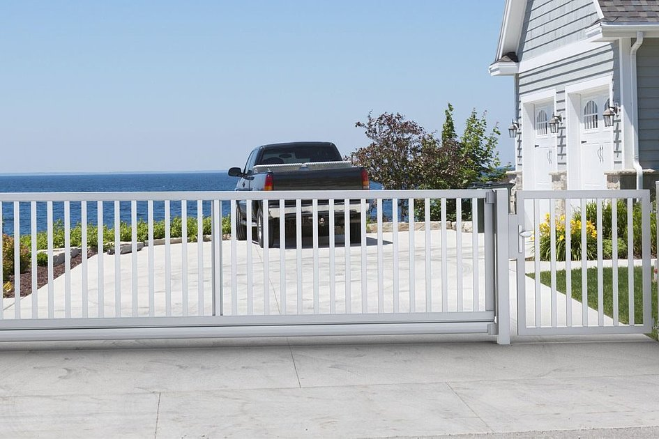 weißer Stabzaun mit Schiebetor und Gartentür vor Haus am Meer