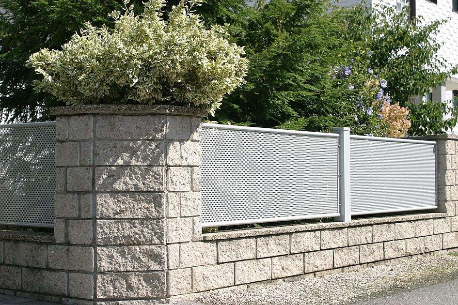 Lochblechzaun aus Aluminium im modernen Design in Mauer eingefasst