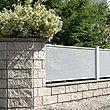 Weißer Gartenzaun mit Lochblech auf Mauersockeln mit Steinziegeln und Pflanzen