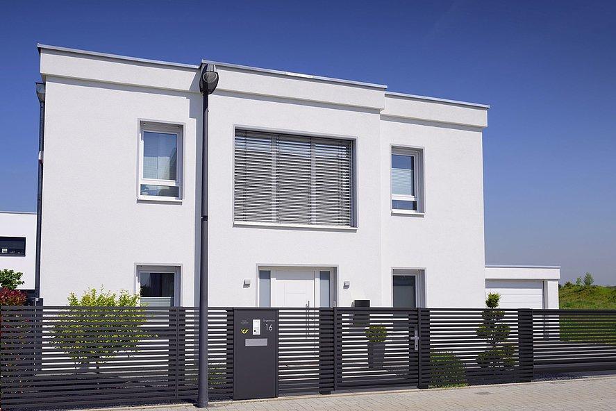 Briefkastensäule intergriert in den modernen Lattenzaun MAGNUS vor modernem zweistöckigen Einfamilienhaus
