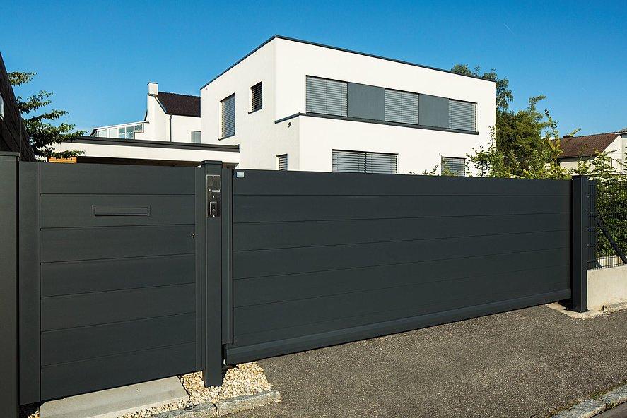 Schiebetor und Gartentür mit Sichtschutz vor modernem Architektenhaus