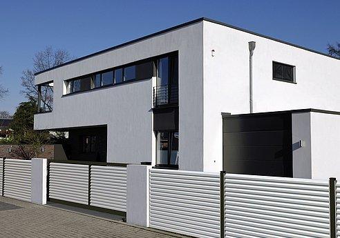Schiebetor und moderner Gartenzaun mit weißen Lamellen vor einem Architektenhaus
