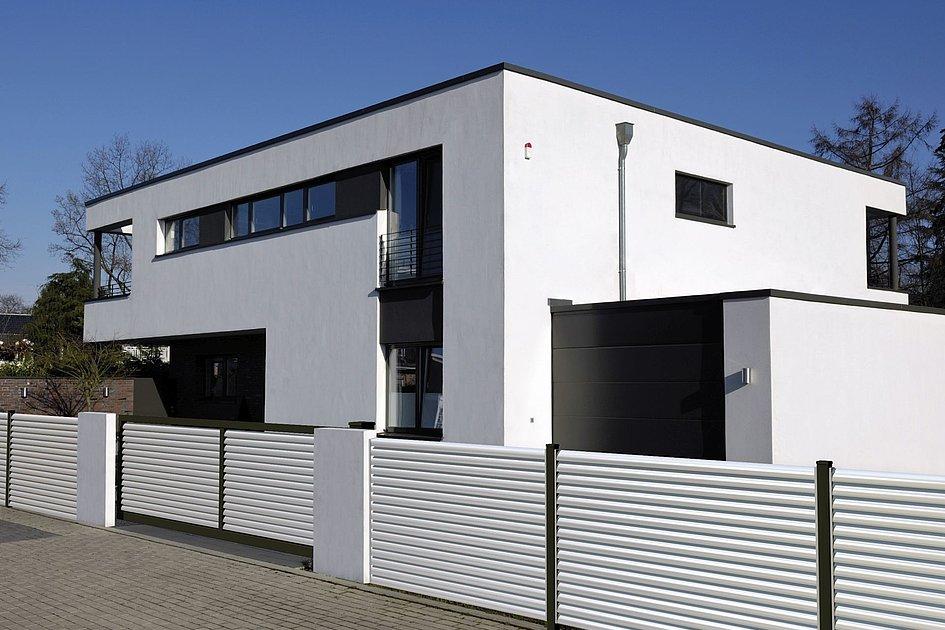moderner Lamellenzaun mit Einfahrtstor in weiß vor moderner Villa