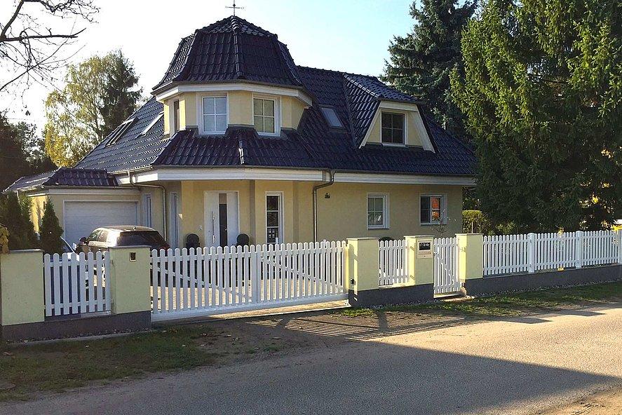 weißer Lattenzaun mit Einfahrtstor vor Gartenvilla mit Schindeldach