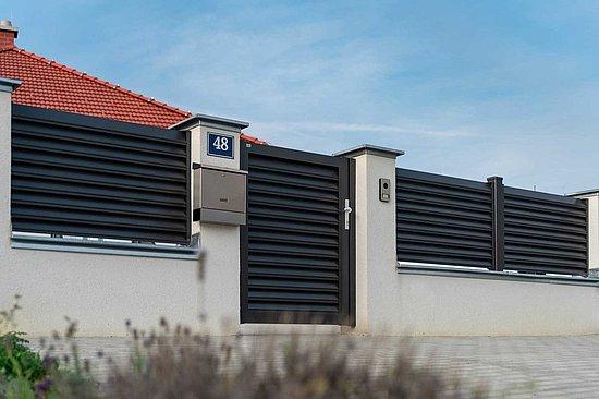 Blick vom Gehweg auf ein mit einem Sichtschutzzaun in anthrazit eingezäunten Haus. In den Zaun ist ein Gartentor des gleichen Modells intergriert