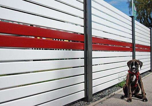 Moderner Sichtschutzzaun aus Aluminium mit Querlatten in weiß und rot, davor sitzt ein Hund